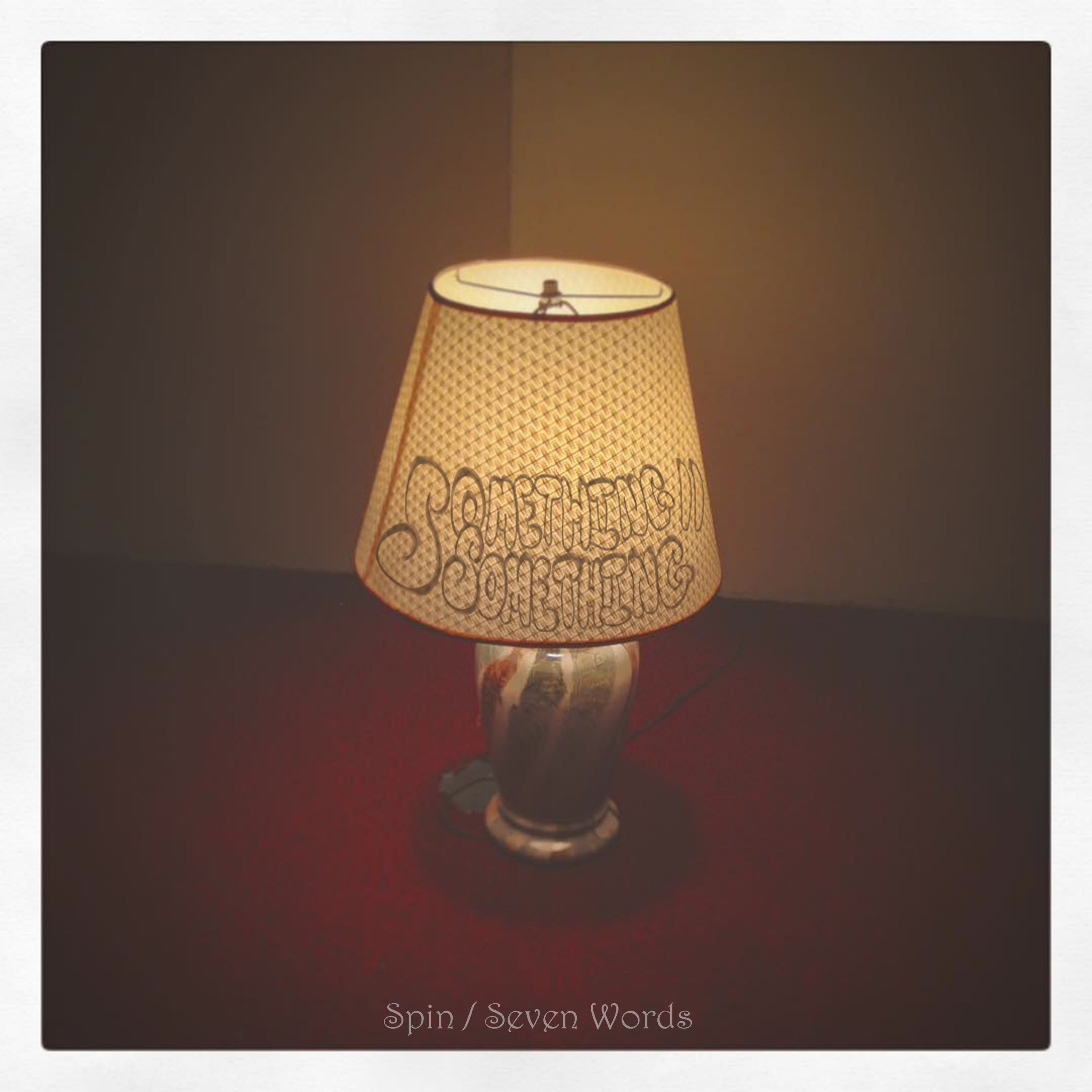 spin seven words single album art is a lamp in an empty room with the something something logo font superimposed onto the lampshade